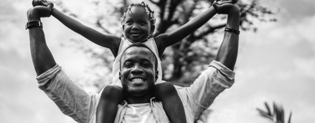 Dad holding his daughter on his shoulders